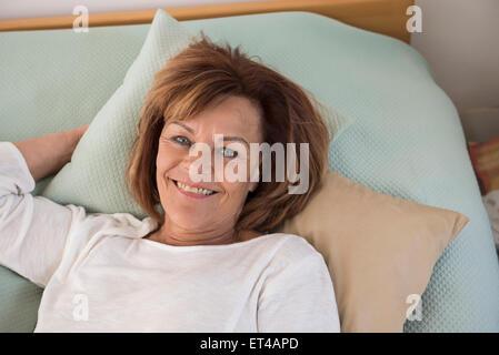 Porträt von senior Frau auf Bett liegend und lächelnd, München, Bayern, Deutschland - Stockfoto