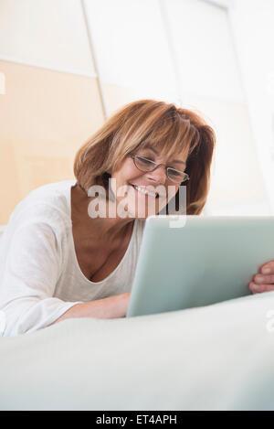 Ältere Frau auf Bett liegend und mit einem digital-Tablette, München, Bayern, Deutschland - Stockfoto