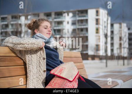 Junge Frau sitzt auf der Bank in der Stadt München Bayern Deutschland Stockfoto