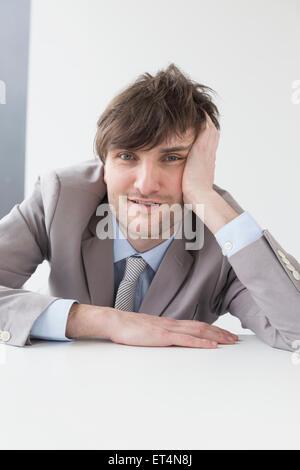 Geschäftsmann, stützte sich auf den Schreibtisch im Büro, Leipzig, Sachsen, Deutschland - Stockfoto