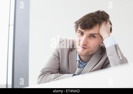 Geschäftsmann, stützte sich auf den Schreibtisch im Büro, Leipzig, Sachsen, Deutschland Stockfoto