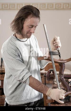 Tischler, Befestigung einen Schraubstock, ein antiker Holzstuhl im Workshop, Bayern, Deutschland - Stockfoto