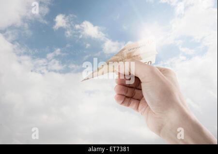 Menschliche Hand mit Papierflieger gemacht aus Geld, Bayern, Deutschland - Stockfoto