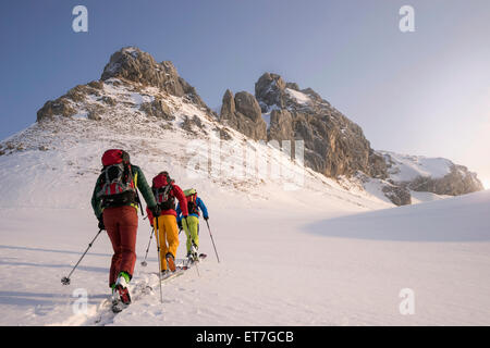Skibergsteiger Klettern auf schneebedeckten Gipfel, Tirol, Österreich - Stockfoto