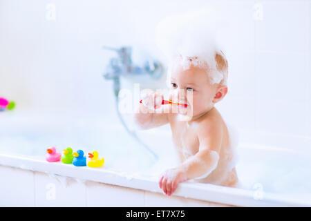 Niedlichen kleinen Jungen seine Zähne putzen, spielen mit Schaum und bunte Kautschuk Ente Spielzeug in einem weißen - Stockfoto