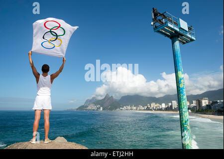 RIO DE JANEIRO, Brasilien - 12. Februar 2015: Athlet in weißer uniform steht eine Olympische Flagge am Arpoador. - Stockfoto