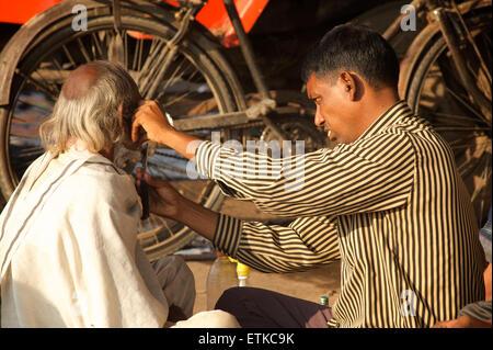 Indische Barbier, dass einem Mann eine Rasur, Jaipur, Rajasthan, Indien - Stockfoto