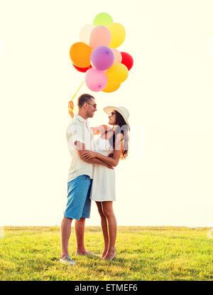 lächelnde paar mit Luftballons im freien - Stockfoto