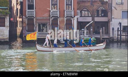 Ein Boot ruderte von sechs Männern und unter der venezianischen Flagge eines geflügelten Löwen bewegt sich entlang - Stockfoto