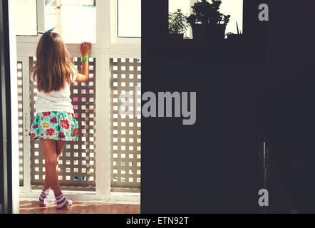 Rückansicht eines Mädchens Blick durch ein Fenster - Stockfoto