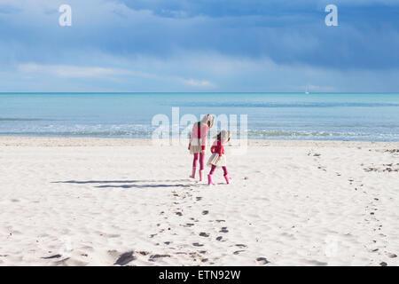 Rückansicht der beiden Mädchen am Strand - Stockfoto