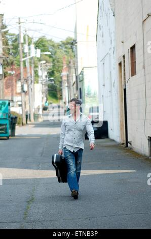 Mann mit Gitarrenkoffer hinunter Alley, Port Angeles, Washington, USA - Stockfoto