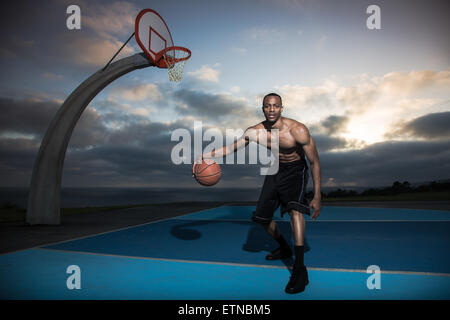 Junger Mann spielen Basketball in einem Park, Los Angeles, Kalifornien, USA - Stockfoto