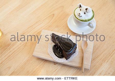 Draufsicht Grüntee Belag von Milch Schaum oben auf die Tasse heißer grüner Tee und Schokolade Kuchen gemacht - Stockfoto