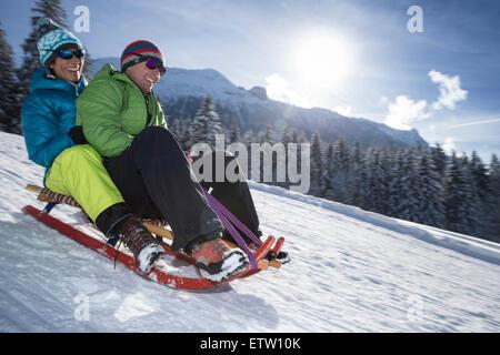Deutschland, Bayern, Inzell, Paare, die Spaß auf einem Schlitten im tief verschneiten Landschaft - Stockfoto