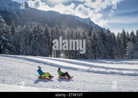 Deutschland, Bayern, Inzell, Paare auf Schlitten im tief verschneiten Landschaft - Stockfoto