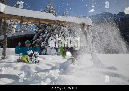 Deutschland, Bayern, Inzell, Paare, die Spaß auf Schaukeln im tief verschneiten Landschaft - Stockfoto