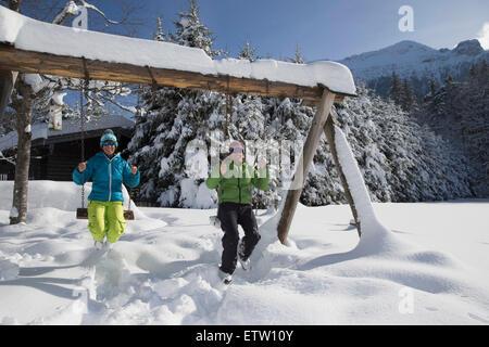 Deutschland, Bayern, Inzell, Paare sitzen auf Schwankungen der tief verschneiten Landschaft - Stockfoto