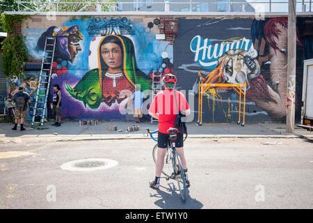 Ein Radfahrer sieht das Werk von Juan und El Niño am Welling Gericht Wandbild-Projekt in der Astoria Nachbarschaft - Stockfoto