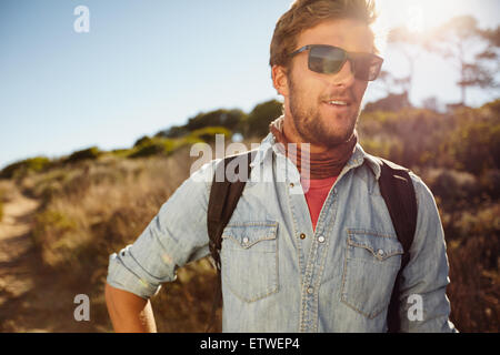Porträt von glücklich Jüngling in der Landschaft wandern. Kaukasische Männermodel mit Rucksack wandern am sonnigen - Stockfoto