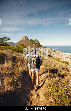 Rückansicht des Paares zu Fuß durch Feldweg am Berg. Junger Mann und Frau Wanderer Wandern in der Natur. Trekking - Stockfoto