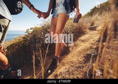 Nahaufnahme des jungen Paares auf einer Wanderung. Bild der junge Mann und Frau Wanderer, Hand in Hand während des Gehens auf Mount beschnitten