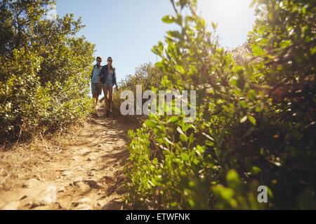 Bild von zwei jungen Menschen, die zu Fuß bergab. Junges Paar Wandern am Berg an einem Sommertag. - Stockfoto