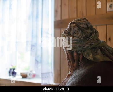 Einzelne alte Frau hält ihren Kopf mit einer einsamen Alter Hand Betrachtung Leben sitzen - Stockfoto