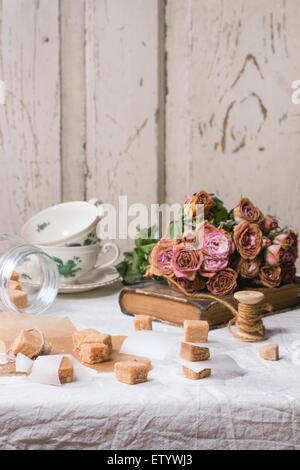 Fudge, Süßigkeiten und Karamell auf Backpapier und in Glas, diente über weiße Tischdecke mit Bouquet von trockenen rosa Rosen und thread Stockfoto