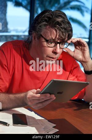 Mann im Urlaub Einstellung überrascht von Detail-Informationen auf seinem iPad Air Tablet-Computer mit iPhone 6 - Stockfoto