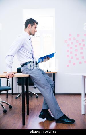Seite Ansicht Porträt eines nachdenklich Geschäftsmann stützte sich auf die Tabelle mit Ordner - Stockfoto