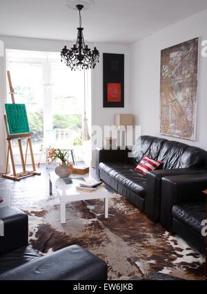 Schwarze Ledersofas und einem weißen Couchtisch im Wohnzimmer des Künstlers mit einem Vintage Kuh Fell Teppich auf - Stockfoto
