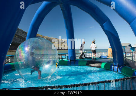 UK, Wales, Conwy, Llandudno North Beach, Pier, junge Wandern am Wasser in Luftpolsterfolie Kugel - Stockfoto