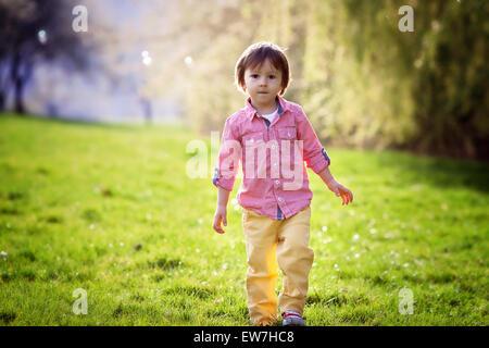 Kleiner Junge, laufen im Park, Seifenblasen, schönen Nachmittag Gegenlicht zu jagen - Stockfoto