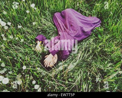 Erhöhten Blick auf eine Frau mit der Hand über ihr Gesicht in der Wiese liegend - Stockfoto