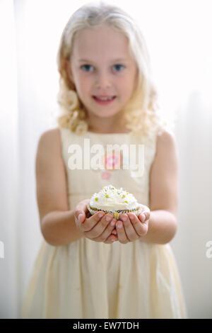 Mädchen hält einen Cupcake mit Gänseblümchen verziert - Stockfoto