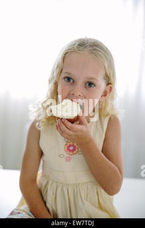 Mädchen essen Zitronen cupcake - Stockfoto