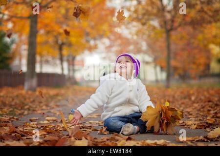 Entzückende kleine Mädchen in den Park, mit Blättern spielen - Stockfoto