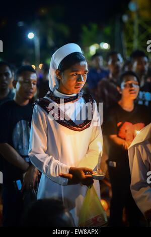 Nonne hält Kerze, wie sie mit anderen Gläubigen in einer Prozession der Semana Santa in Larantuka, Insel Flores, - Stockfoto