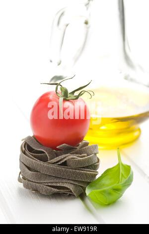 Tagliatelle-Nudeln mit Tomaten und Basilikum Blatt am Küchentisch - Stockfoto