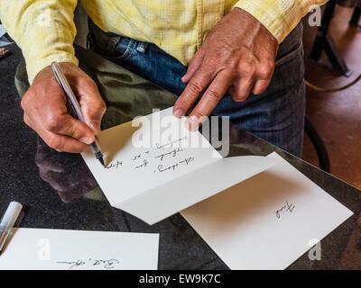 Ein Mann mit verwitterten Händen schreibt ein Dankesschreiben in schöne Schreibschrift schreiben an einen Kunden, - Stockfoto