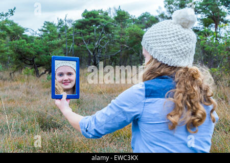 Niederländische Teenager Blondine mit langen Haaren in Spiegel mit Wald-Hintergrund - Stockfoto