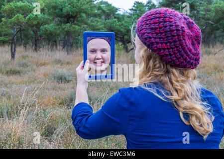Niederländische Teenager-Mädchen halten Spiegel in der Natur und sich selbst zu betrachten - Stockfoto