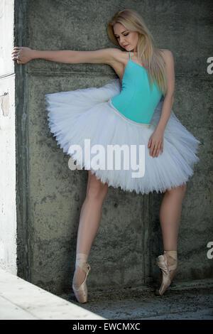 Anmutige Tänzerin mit blonden Haaren auf dem Hintergrund der grauen Bereitung Stockfoto