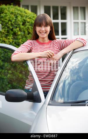 Lächelnde junge Frau stand neben dem Auto - Stockfoto