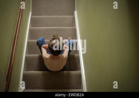 Ein Kind sitzt auf der Treppe mit dem Kopf in seine Hände suchen verärgert