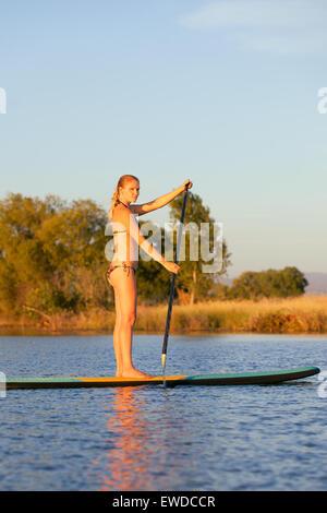 Eine junge Frau in Badebekleidung Paddeln ein Stand Up Paddle Board auf einem kleinen See im nördlichen Kalifornien - Stockfoto