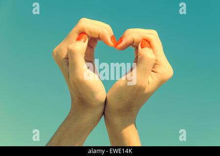 Retro-Filter Mädchen Hände In Herzform auf blauen Himmel - Stockfoto