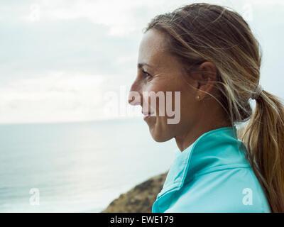 Eine lächelnde junge Frau, Seitenprofil in blau oben ausgeführt - Stockfoto