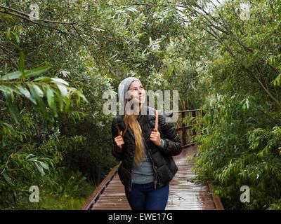 Lächelnde junge Frau zu Fuß durch den Wald in einem park - Stockfoto